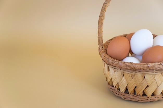 Biało-brązowe jajka w wiklinowym koszu na pastelowym beżowym tle. jaja kurze świeże. wesołych świąt z miejsca na kopię.