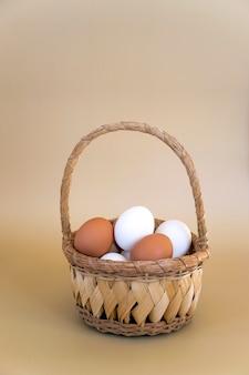 Biało-brązowe jajka w wiklinowym koszu na pastelowym beżowym tle. świeże jaja kurze, kompozycja wielkanocna.