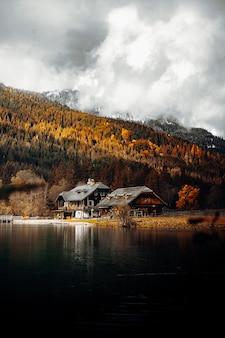 Biało-brązowy dom w pobliżu jeziora i zielonych drzew pod białymi chmurami i błękitnym niebem podczas