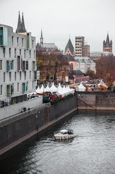 Biało-czarna łódź na rzece w pobliżu betonowego budynku