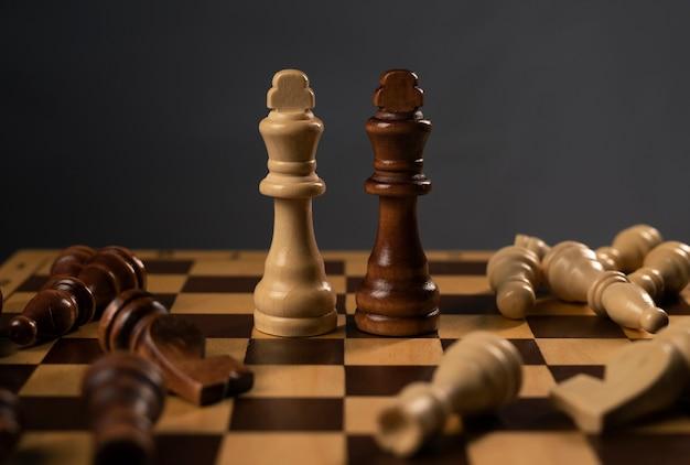 Biało-czarni królowie szachowi stojący wśród upadłych postaci. rysuj na szachownicy.