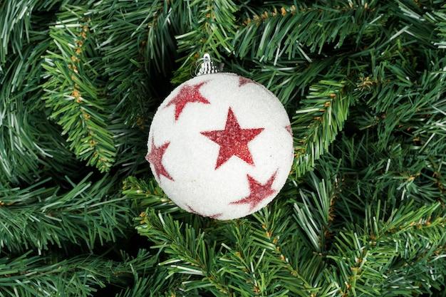Biało-czerwona piłka boże narodzenie na białym tle na gałęzi choinki.