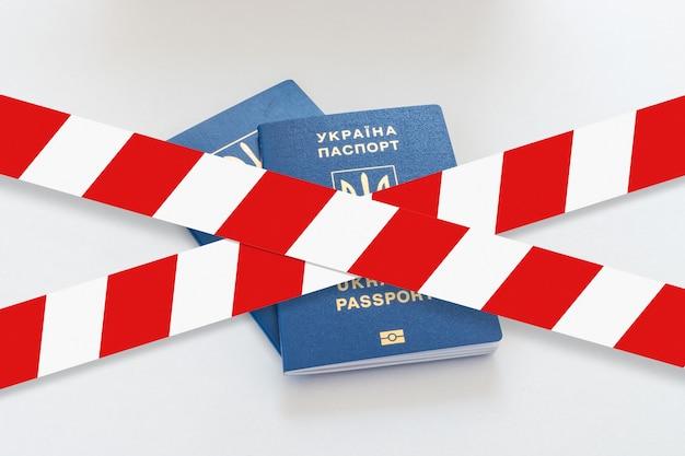 Biało-czerwona taśma ostrzegawcza nad dwoma paszportami ukrainy