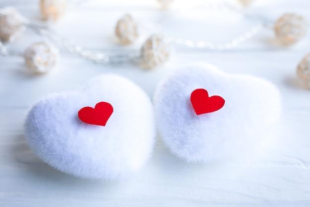 Biało -czerwone serca na drewnianym tle. koncepcja dzień świętego walentego. miłość i romantyczne zdjęcie. pocztówka na wakacje. małe rustykalne światła.