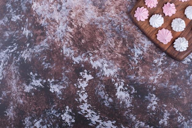 Biało-różowe pianki w kształcie kwiatków na drewnianym talerzu.