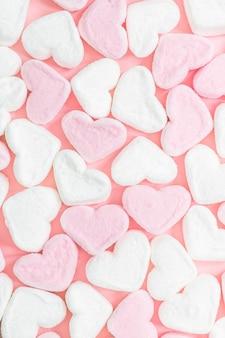 Biało-różowe pianki w kształcie serca na różowym tle