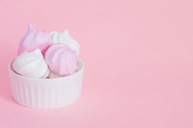 Biało-różowe skręcone bezy w porcelanowej misce na różowo