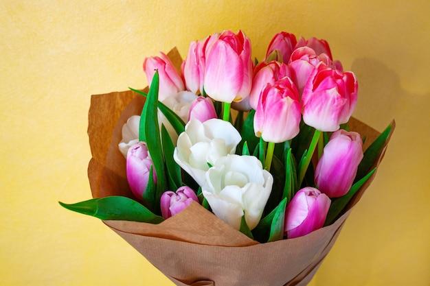 Biało-różowe tulipany holenderskie zawinięte w papier pakowy na żółtym tle