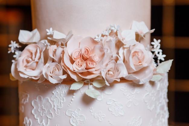Biało-różowy piękny tort weselny na tle łuku weselnego wieczorem. przegrana