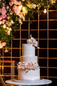 Biało-różowy piękny tort weselny na tle łuku weselnego wieczorem.