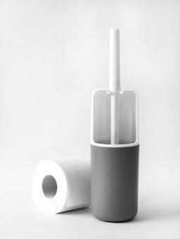 Biało-szara plastikowa szczotka toaletowa i rolka papieru toaletowego na białym tle