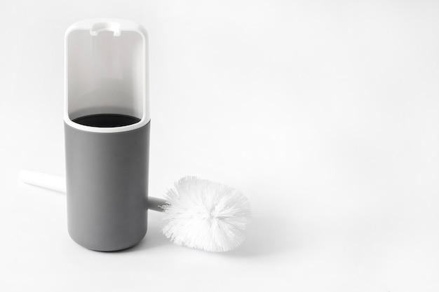 Biało-szara plastikowa szczotka toaletowa na białym tle z miejscem na kopię