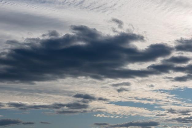 Biało-szare chmury na niebie oświetlonym przez zachodzące słońce. jasnoniebieskie niebo za ciemnymi i dramatycznymi chmurami burzowymi. idealne naturalne tło nieba, makiety do projektu