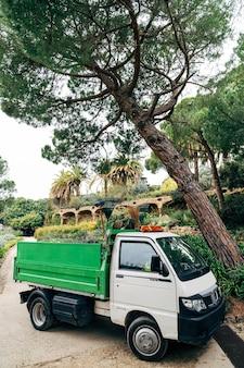 Biało-zielona komercyjna mini-ciężarówka o średniej ładowności. samochód ogrodnik w parku.