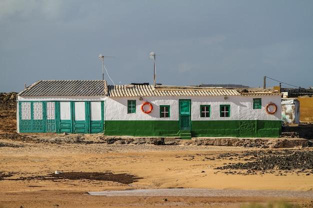 Biało-zielony budynek na środku pola na fuerteventurze