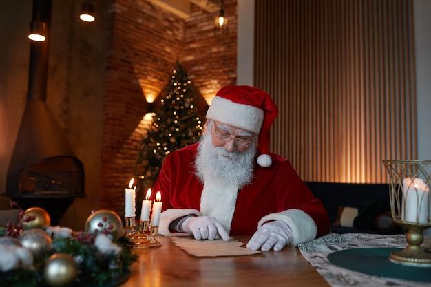 Białobrody mikołaj w czapce i rękawiczkach siedzi przy stole w przytulnym pokoju i czyta list pod ok...