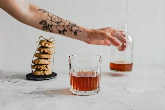 Białoruś, mińsk - 19.06.2020: szklanka zimnej kawy parzonej, stos ciasteczek owsianych i ręka z tatuażem z kwiatem trzymająca butelkę