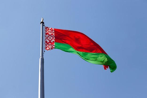 Białoruska flaga państwowa na błękitnym niebie