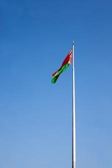 Białoruska flaga państwowa na tle błękitnego nieba, oficjalna flaga państwowa republiki białorusi