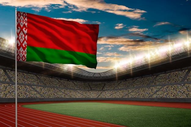 Białoruska flaga przed stadionem lekkoatletycznym z kibicami.