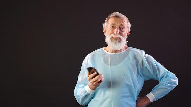 Białowłosy lekarz, chirurg w garniturze medycznym używa smartfona na odosobnionej ciemnej przestrzeni i patrzy w kamerę.