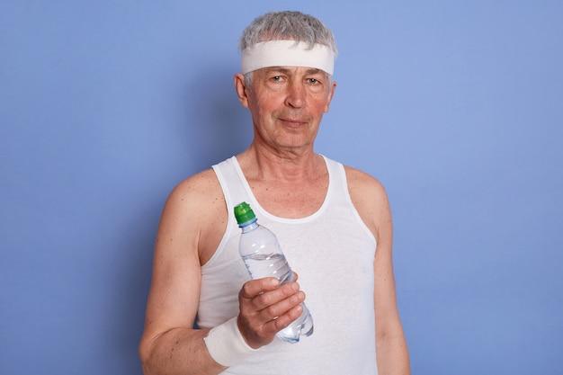 Białowłosy starszy mężczyzna sportowca, mając przerwę między zestawami podczas treningu, trzymając butelkę wody, pozowanie w białej odzieży na białym tle.