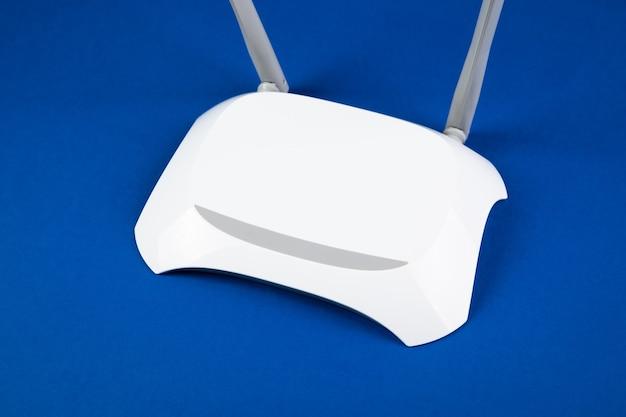 Biały adapter wi-fi na niebieskiej powierzchni
