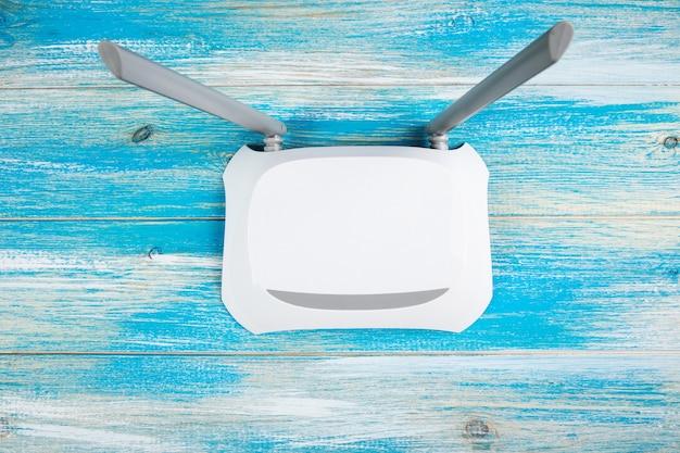 Biały adapter wifi na niebieskiej drewnianej powierzchni