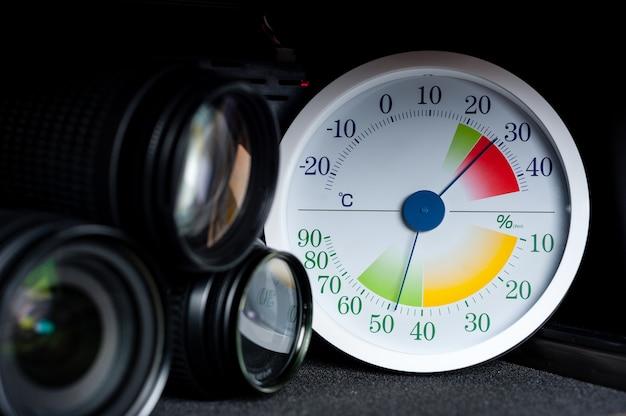 Biały analogowy termometr i higrometr z wyposażeniem fotograficznym.
