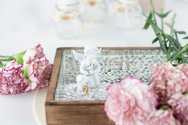 Biały anioł na biurku. piękne różowe kwiaty na białym biurku.