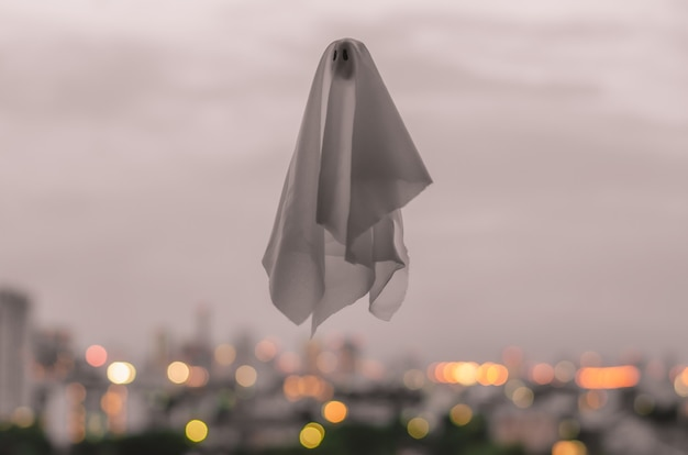 Biały arkusz ducha latający w zmierzchu niebie. koncepcja halloween.