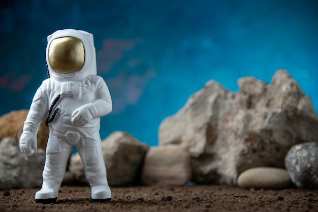 Biały astronauta ze skałami na księżycu niebieska powierzchnia fantasy kosmiczna sci fi