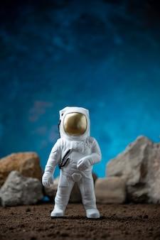 Biały astronauta ze skałami na księżycu niebieski fantasy kosmiczny sci fi
