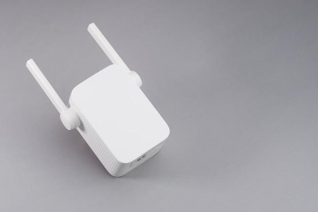 Biały bezprzewodowy repeater wifi na szarym tle.
