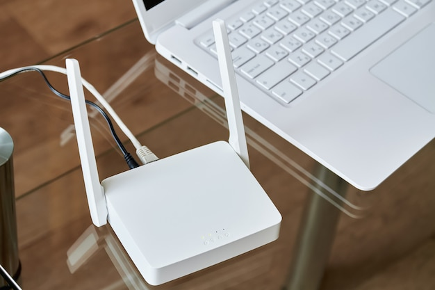 Biały bezprzewodowy router wi-fi w pobliżu laptopa na szklanym stole