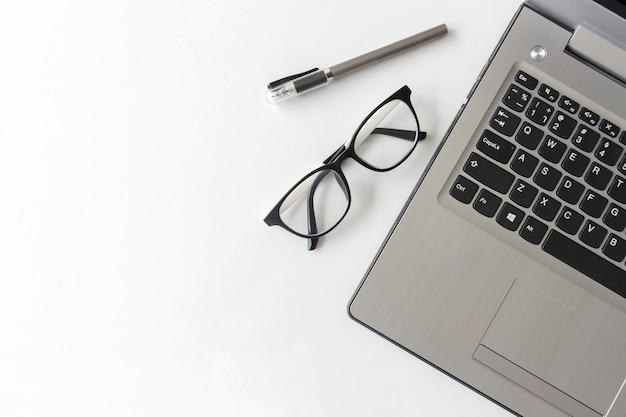 Biały biurko stół z materiałów biurowych notebook i okulary