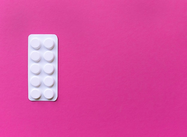 Biały blister tabletek na różowym tle. proste mieszkanie z pastelową teksturą z miejscem na kopię. pojęcie medyczne.