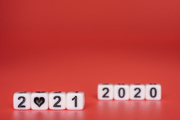 Biały blok z numerami 2021 i 2020 na czerwonej powierzchni.