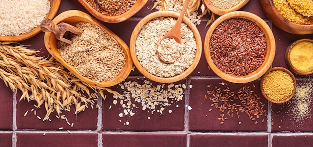 Biały, brązowy i czerwony ryż, kasza gryczana, kasza jaglana, kasza kukurydziana, quinoa i bulgur w drewnianych miskach na jasnoszarym kuchennym stole. płatki bezglutenowe. widok z góry z copyspace. transparent.