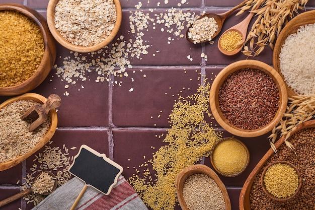 Biały, brązowy i czerwony ryż, kasza gryczana, proso, kasza kukurydziana, quinoa i bulgur w drewnianych miskach na brązowym kamiennym stole kuchennym. płatki bezglutenowe. widok z góry z copyspace