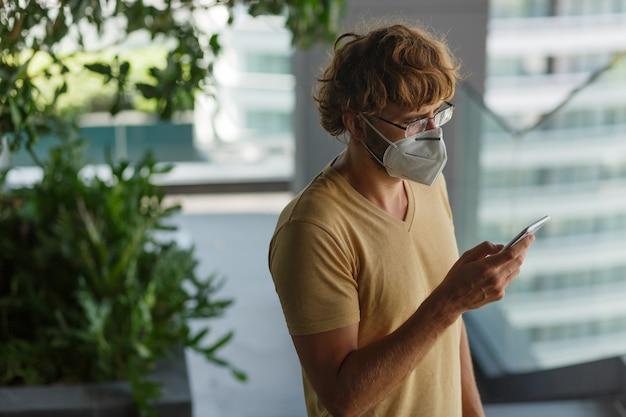 Biały brodaty dorosły mężczyzna za pomocą smartfona podczas noszenia maski chirurgicznej na ścianie przemysłowej. zdrowie, epidemie, media społecznościowe.