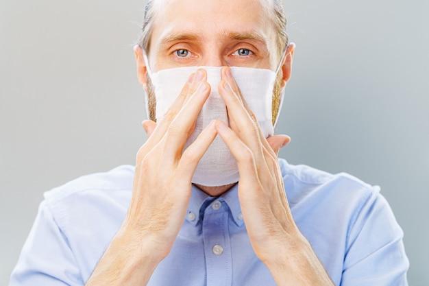 Biały brodaty mężczyzna w niebieskiej koszuli nakłada maskę przed zanieczyszczeniem powietrza i koronawirusem covid-19.