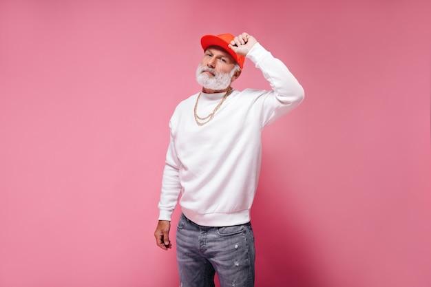 Biały brodaty mężczyzna w pomarańczowej czapce pozuje na różowej ścianie