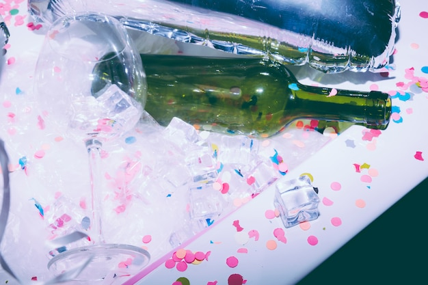 Biały brudny stół z pustym kieliszkiem; zielona butelka alkoholu; kostki lodu i konfetti po przyjęciu urodzinowym