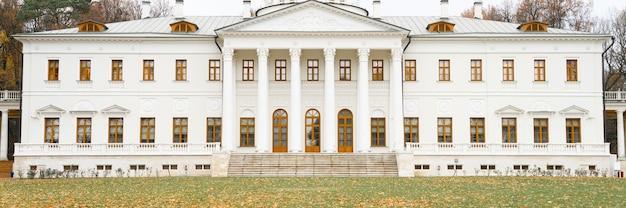 Biały budynek osiedla z kolumnami i jesienią opadłych liści klonu na ziemi w jesiennym parku. transparent