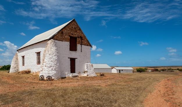 Biały budynek w polu farmy na obszarach wiejskich pod zachmurzonym niebem