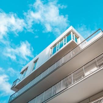 Biały budynek z balkonami i niebieskim niebem