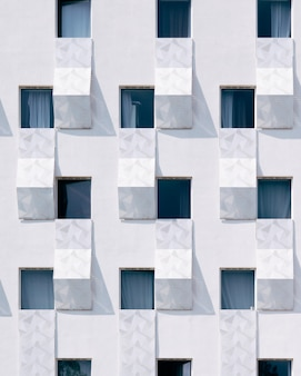 Biały budynek z niebieskimi oknami