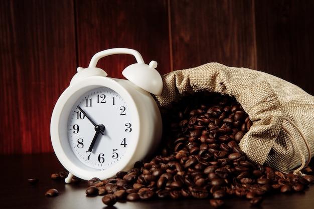Biały budzik i ziarna kawy w torbie na drewnianym stole zbliżenie.