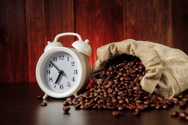 Biały budzik i ziarna kawy w torbie na drewnianym stole.